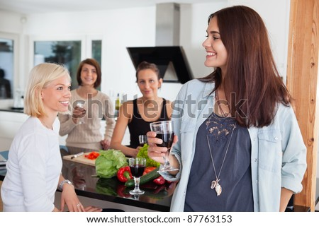 Group of happy female friends enjoying drink in kitchen - stock photo