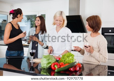 Group of happy female friends in kitchen - stock photo