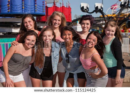 Group of 8 happy female teens at an amusement park - stock photo