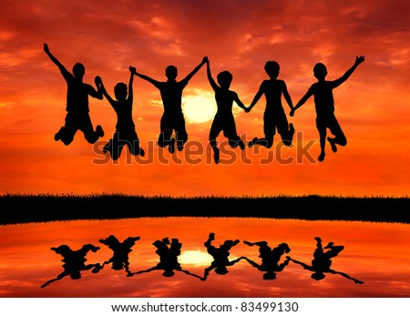group of happy freedom men and women friends jumping with joy at sunrise silhouetted - stock photo