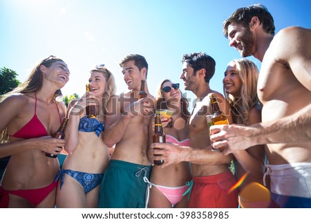 Group of happy friend holding beer bottles and glass of cocktail near pool - stock photo