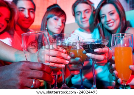 Group of happy friends at a bar or a nightclub toasting - stock photo