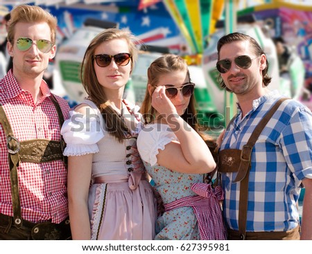 Group of happy friends celebrating Oktoberfest posing in front of a carousel wearing traditional tracht and sunglasses