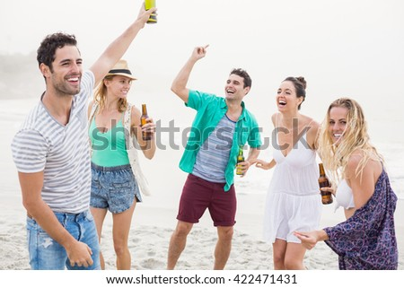 Group of happy friends dancing on the beach with beer bottles