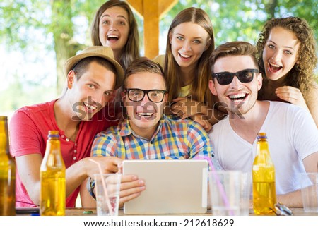 Group of happy friends drinking and having fun with tablet in pub garden - stock photo