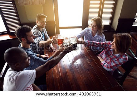 Group of happy friends drinking beer in pub