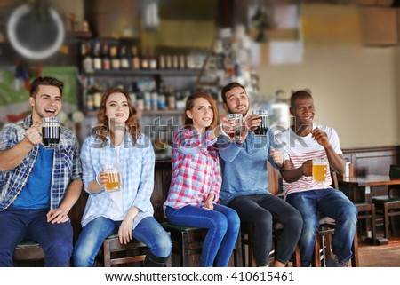Group of happy friends drinking beer in pub - stock photo