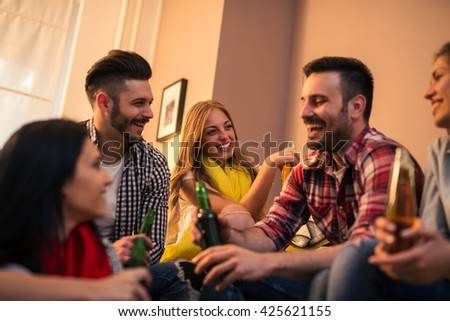 Group of happy friends enjoying a home party together. - stock photo