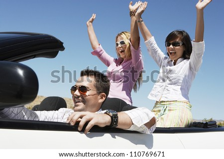 Group of happy friends enjoying their journey in car - stock photo