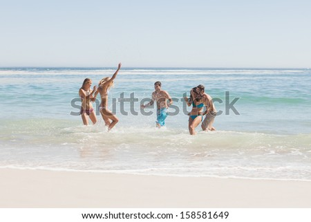 Group of happy friends having fun on the beach on holidays - stock photo