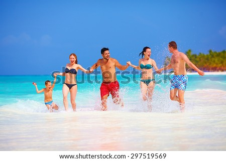 group of happy friends having fun together on tropical beach - stock photo