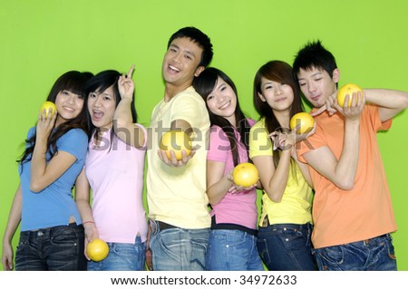 group of happy friends holding grapefruit on their hands