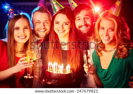 Group of happy friends in birthday caps looking at camera