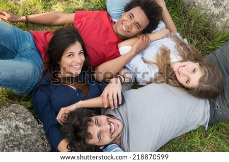 Group Of Happy Friends In Casual Lying On Grass Looking At Camera - stock photo