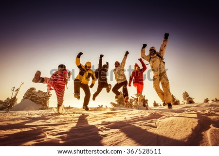 Group of happy friends jumps on background of sunset. Sheregesh resort, Siberia, Russia - stock photo