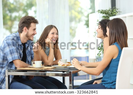 Group of 4 happy friends meeting and talking and eating desserts on a table at home - stock photo