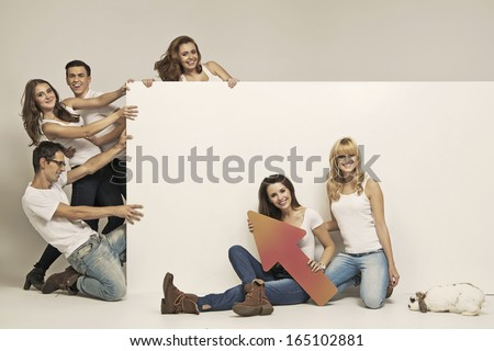 Group of happy friends presenting advert