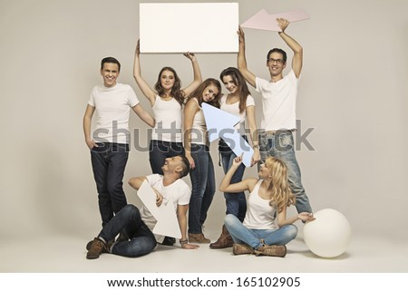 Group of happy friends presenting advert - stock photo