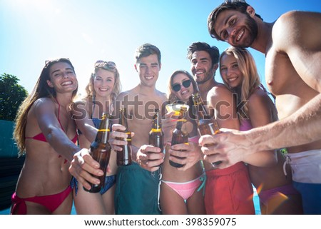Group of happy friends showing beer bottles near the pool on a sunny day