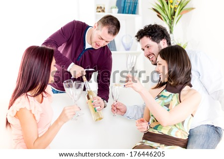 Group of happy friends sitting and drinking White Wine at Home Interior. - stock photo