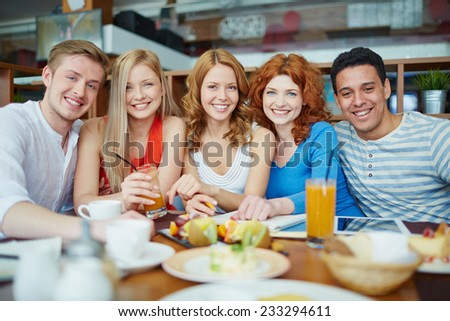 Group of happy friends sitting at cafe - stock photo