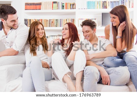 group of happy friends sitting on sofa talking and smiling - stock photo