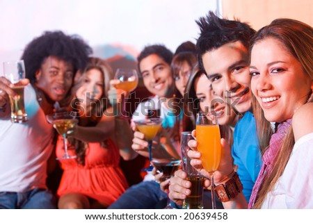 group of happy friends smiling in a bar or a nightclub - stock photo
