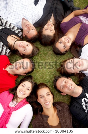 group of happy friends smiling together on the floor