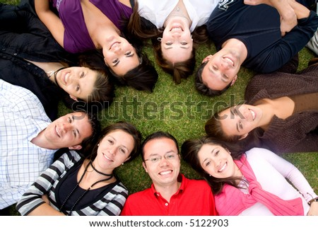 group of happy friends smiling with heads together on the floor - stock photo