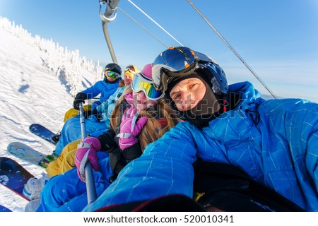 Group of happy friends snowboarding doing selfie at winter resort