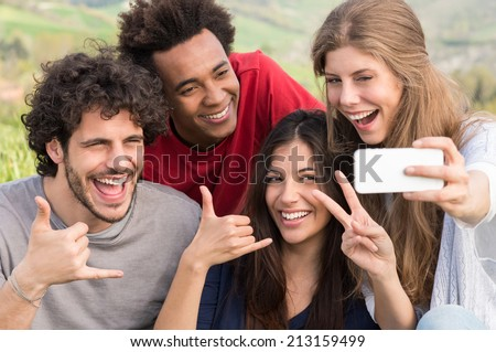 Group Of Happy Friends Taking Picture With Mobile Phone Outdoor - stock photo