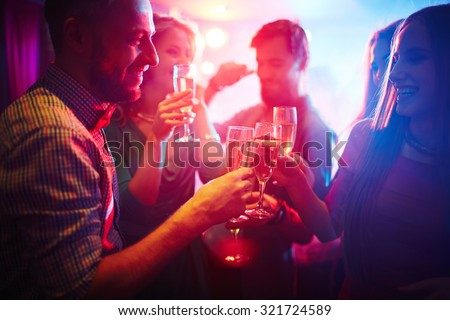 Group of happy friends toasting at party with champagne