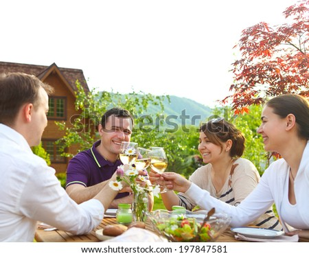 Group of happy friends toasting wine glasses in the garden while having lunch - stock photo