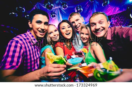 Group of happy friends toasting with cocktails at party - stock photo