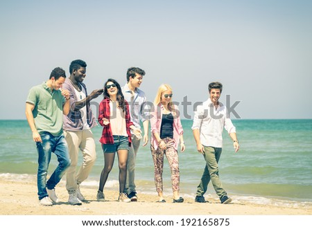 Group of happy friends walking a talking at the beach - Concept of international multiracial friendship - Retro nostalgic filtered look - stock photo