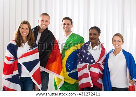 Group Of Happy Friends With Flags From Different Countries - stock photo