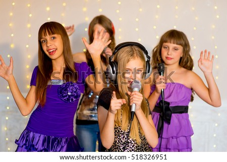 Group of happy girls singing together on karaoke on background of lights with first plan of one girl