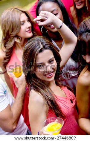 group of happy girls smiling at a party with some cocktail drinks - stock photo