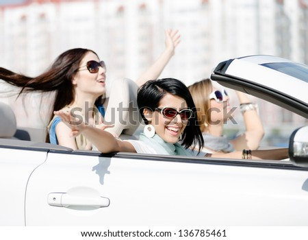 Group of happy girls with outstretched arms in the car. Little trip of teenage ladies - stock photo
