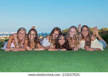 group of happy healthy teen girls smiling laying on grass - stock photo