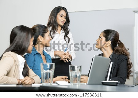 Group of happy Indian business women in a meeting at office - stock photo