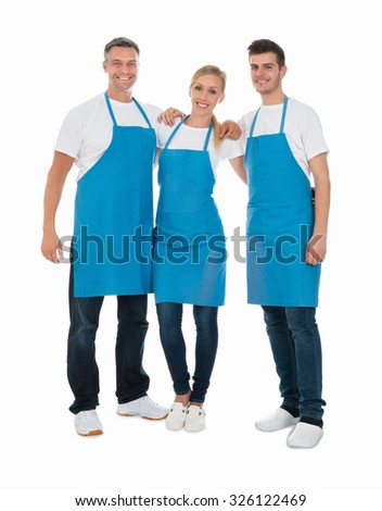 Group Of Happy Janitors Wearing Blue Apron Over White Background - stock photo