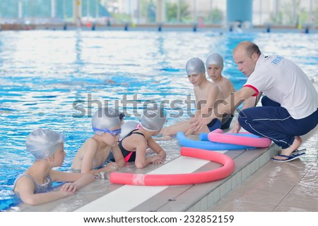 group of happy kids children at swimming pool class learning to swim - stock photo