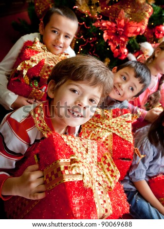 Group of happy kids holding Christmas presents and smiling