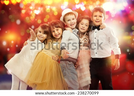 Group of happy kids in celebratory clothes with colorful lights on background. Holidays, christmas, new year, x-mas concept. - stock photo