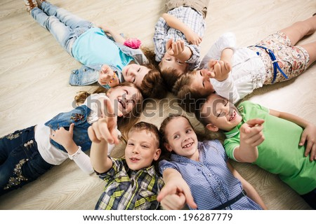 Group of happy kids laying in star shape on the floor with lifted hands - stock photo