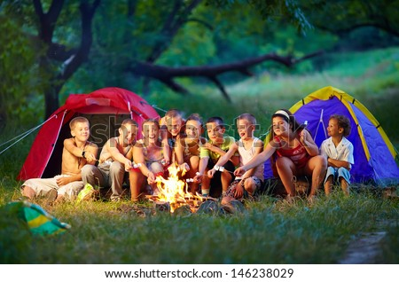 group of happy kids roasting marshmallows on campfire - stock photo