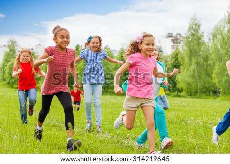 Group of happy kids running through green field - stock photo