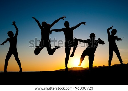 group of happy kids silhouettes jumping on the beach on beautiful summer sunset