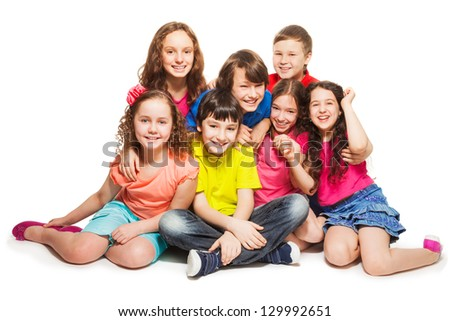Group of happy kids sitting together hugging and smilng